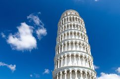 Leaning Tower Torre di Pisa on Piazza del Miracoli square, blue sky with white clouds background royalty free stock photo