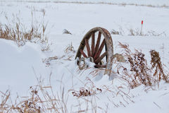Leaning wagon wheel. Weathered wood wagon wheel in a snow drift Stock Photo