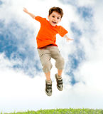 Leap. Photo of young boy jumping and raising hands in outside Stock Photography