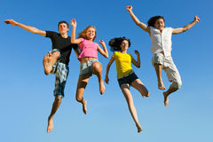 Leap ahead against the sky. Four young boys and girls jumping on a background of blue sky Royalty Free Stock Photos