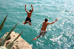 Leap of faith. Two boys jumping into water from a rock stock photo