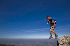 A leap of faith. Leap of faith - A mountaineer jumping trough the rocks, over a clear blue sky Royalty Free Stock Photos