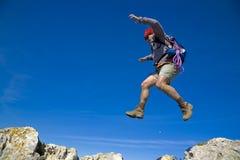 A leap of faith. Leap of faith - A mountaineer jumping trough the rocks, over a clear blue sky Stock Photo