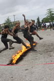 Leap of Faith. Five  women leap the Pyromaniac fire obstacle.  Rugged Maniac Competition, August 15, 2015, Vancouver, BC Royalty Free Stock Image