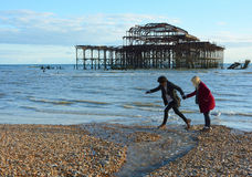 Lovers Leap. A romantic couple stroll along the beach but have to leap across running water with the backdrop of Brightons relic, the West Pier. A Metaphor Royalty Free Stock Photography