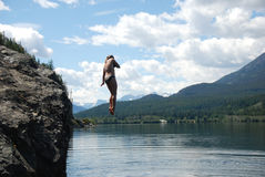 Leaping. A woman leaping into the lake stock photos