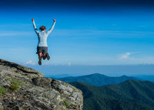 Leaping for Joy from a Rocky Overlook. In summer Royalty Free Stock Photography