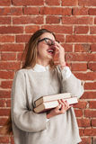 Leaping laughing young woman with books Royalty Free Stock Photography