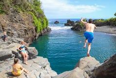 Leaping into Maui's tropical Venus Pool swimming hole.