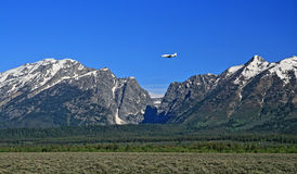 Lear Jet flying into Jackson Hole Airport next to the Grand Tetons Mountain Range in Wyoming Royalty Free Stock Photo