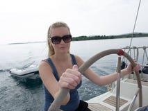 learing对风帆的白肤金发的妇女在克罗地亚 免版税库存图片