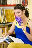 Learing Into a Library. A smiling woman in a library holding a hyacinth Royalty Free Stock Photography