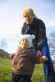Learing to walk. Young mother holding baby up as she teaches him to walk in countryside Stock Photos