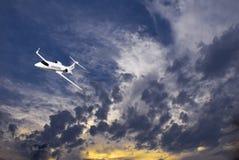 Learjet 45 avec des nuages de coucher du soleil Photos stock