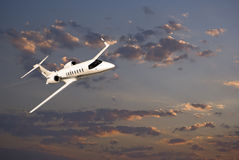 Learjet 45 avec des nuages de coucher du soleil Photographie stock libre de droits