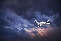 Learjet 45 with Storm Clouds. Business jet (Learjet 45) zipping through the skies, with storm building in the clouds in the background Royalty Free Stock Images