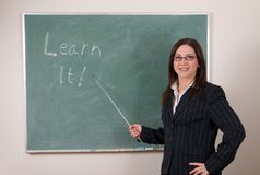 Learn it!. Attractive young woman teacher points to inspirational message on green chalkboard, learn it Royalty Free Stock Image
