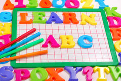 Learn abc background. Board with colorful magnetic letters that spell Learn abc Royalty Free Stock Photos