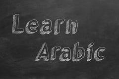 Learn Arabic. Hand drawing `Learn Arabic` on blackboard royalty free illustration