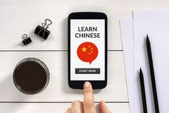 Learn Chinese concept on smart phone screen with office objects. On white wooden table. All screen content is designed by me. Flat lay Royalty Free Stock Photos