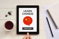 Learn Chinese concept on tablet screen with office objects. On white wooden table. All screen content is designed by me. Flat lay Royalty Free Stock Images