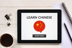Learn Chinese concept on tablet screen with office objects. On white wooden table. All screen content is designed by me. Flat lay Royalty Free Stock Photography