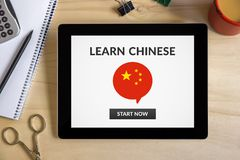 Learn Chinese concept on tablet screen with office objects. On wooden desk. All screen content is designed by me. Top view Stock Photos