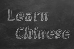Learn Chinese. Hand drawing `Learn Chinese` on blackboard stock illustration
