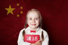 Learn chinese language. Smart child student on Chinese flag. Background stock image