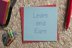 Learn and Earn written on a note. Top view of Learn and Earn written note on the wood chippings board Stock Photo
