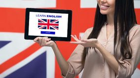 Learn English app on tablet screen in female hand, Great Britain flag background. Stock footage stock video