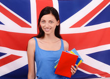 Learn English. Beautiful student holding books, red blank book cover. Stock Photo