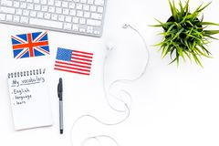 Learn english concept. British and american flags, computer keyboard, headphones, notebook for new vocabulary on white. Background top view Stock Photo
