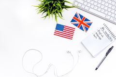 Learn english concept. British and american flags, computer keyboard, headphones, notebook for new vocabulary on white. Background top view Royalty Free Stock Images