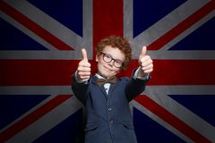 Learn English concept. Child boy student having fun and showing thumb up on the UK flag background.  stock photography