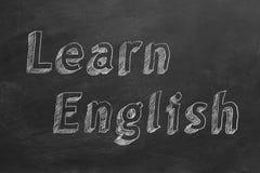 Learn English. Hand drawing `Learn English` on blackboard stock illustration