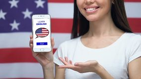 Learn English language app on cellphone in female hand, USA flag on background. Stock footage stock video