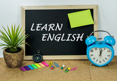 LEARN ENGLISH. LEARN ENGLISH on black board with compass and clock Royalty Free Stock Images