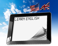 Learn English - Tablet Computer. Black tablet computer with pages and phrase learn english on display, british and usa flags on a blue sky Royalty Free Stock Photo