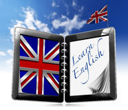 Learn English - Tablet Computer. Black tablet computer with two pages and word learn english on display and british flag on a blue sky Stock Photography