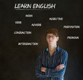 Learn English teacher with chalk background. Learn English confident handsome man teacher with arms folded and glasses chalk blackboard background stock images