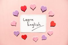 Learn English - text on white paper on pink background with heatrs, studying language stock photo