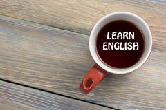 Learn English Text written on coffee cup. Office desk table top view Royalty Free Stock Photo