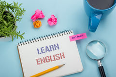 Learn English Text written on notebook page, red pencil and coffee cup. Office desk table top view Stock Photo