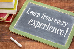 Learn from every experience. White chalk text on a slate blackboard with a stack of books against rustic wooden table stock photography