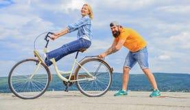 Learn faisant un cycle avec l'appui La femme monte le fond de ciel de bicyclette Les aides d'homme gardent l'équilibre et montent photos libres de droits