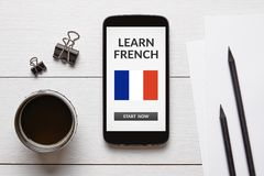 Learn French concept on smart phone screen with office objects. On white wooden table. All screen content is designed by me. Flat lay Stock Photography