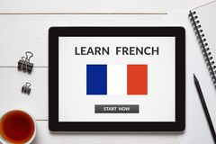 Learn French concept on tablet screen with office objects. On white wooden table. All screen content is designed by me. Flat lay Royalty Free Stock Photos