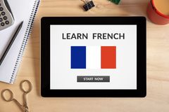 Learn French concept on tablet screen with office objects. On wooden desk. All screen content is designed by me. Top view Stock Images
