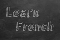 Learn French. Hand drawing `Learn French` on blackboard royalty free illustration